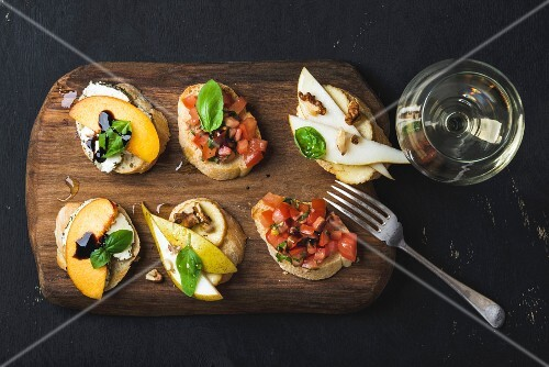 Bruschetta with fruits and tomatoes served with a glass of white wine