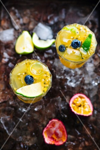 An orange drink with passionfruit, lime and blueberry