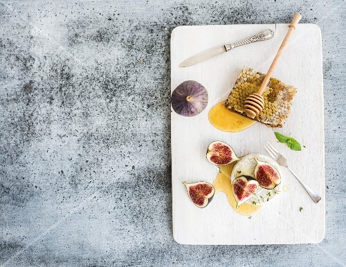 Camamber cheese with figs and honey comb on white painted wooden board over grey grunge background