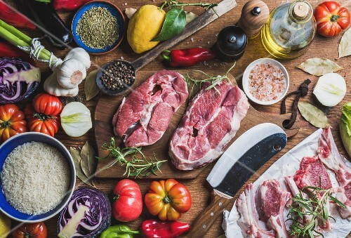 Ingredients for cooking meat dinner: Raw uncooked lamb meat assortment, rice, olive oil, spices and vegetables