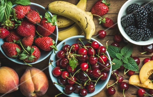 Summer fresh fruit and berry variety over wooden backdrop