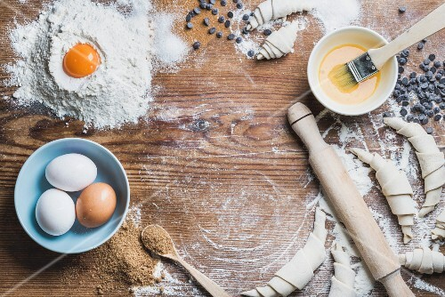 Backzutaten für Croissants: Brauner Zucker, Eier, Mehl, Butter und Schokodrops auf Holzuntergrund