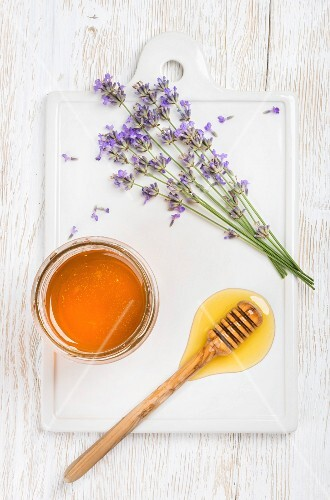 Lavender honey in glass jar and on a honey drizzler next to fresh lavender flowers on ceramic board