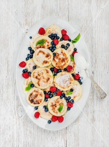 Russian and Ukranian cuisine: Syrniki or cottage cheese pancakes with fresh forest berries and sour cream sauce
