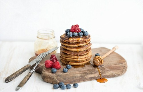 Homemade pancakes with fresh garden berries, honey on wooden board over white painted wooden background