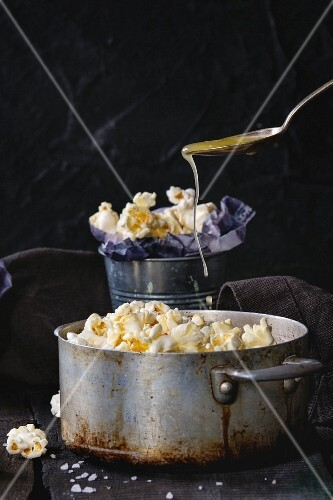Prepared buttered popcorn served with sea salt in small buckets and vintage aluminum pan on old wooden kitchen table