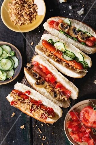 Assortment of homemade hot dogs with sausage, fried onion, tomatoes and cucumber, served with ingredients