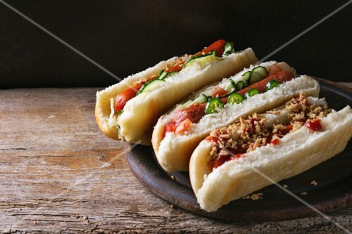 Assortment of homemade hot dogs with sausage, fried onion, tomatoes and cucumber, served on wood chopping board