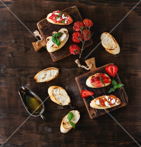 Assorted bruschetta with tomatoes, strawberries, feta cheese, chicken, mushrooms and basil on a wooden surface