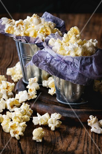 Prepared salted popcorn served in small buckets with paper inside on wood chopping board