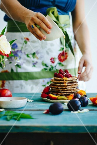 Girl with flower apron pours honey over pancakes