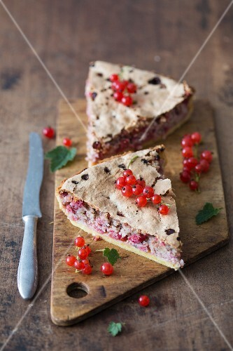 Slices of redcurrant & almond tart on a wooden cutting board