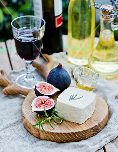 Goats' cheese, fresh figs and honey on a wooden board