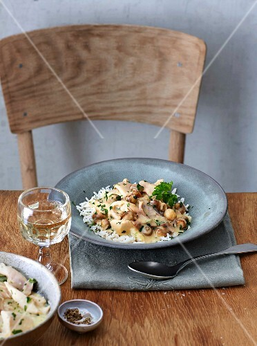 Chicken fricassée with mushrooms on a rustic wooden table
