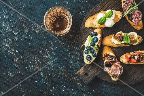 Italian crostini with various toppings on round wooden board and glass of rose wine