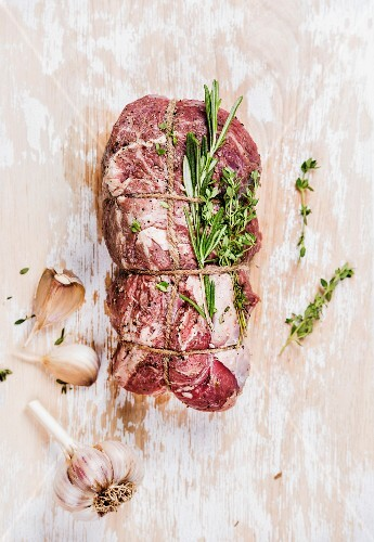 Raw uncooked roastbeef meat cut with rosemary, thyme and garlic on old white painted wooden background