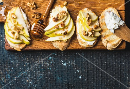 Crostini with sliced pear, ricotta, honey and walnuts
