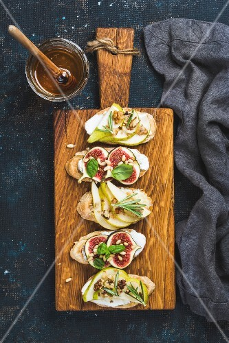 Crostini with pear, ricotta cheese, honey, figs, nuts and herbs