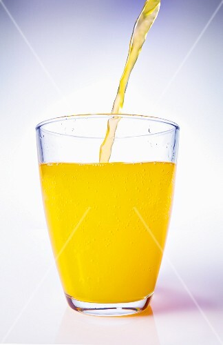Orange Juice Pouring into a Stem Glass