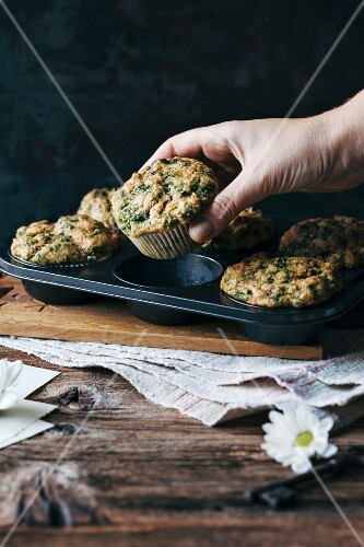 Female hand taking a savoury chard muffin out of the baking pan