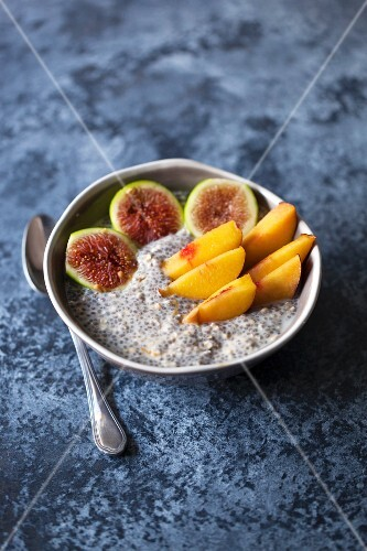 Healthy chia pudding topped with sliced fresh figs and peaches