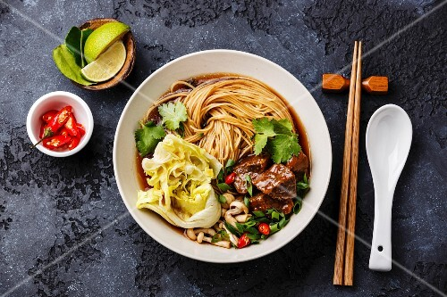 Spicy asian noodles in broth with Beef on dark background