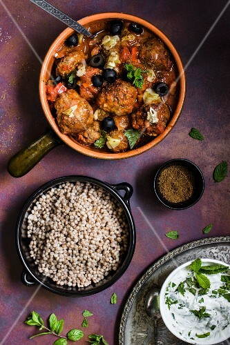 Moroccan lamb meatballs in a spicy tomato sauce with caraway, garlic and olives next to a bowl of giant couscous