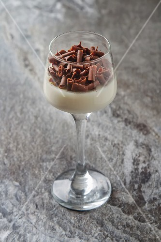 Panna cotta with chocolate curls in a dessert glass
