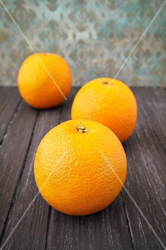 Three oranges on a wooden surface
