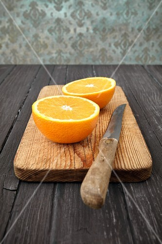 An orange cut in half with a knife on a wooden chopping board