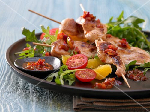Chicken kebabs on a bed of rocket and tomato salad