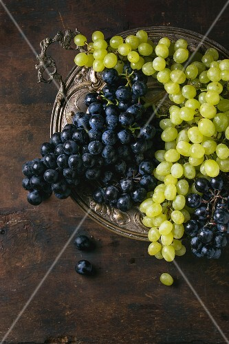 Red and white grapes in an old metal dish on a wooden surface