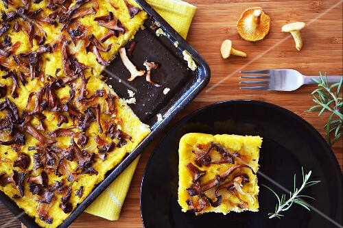 Polenta cake with chanterelle mushrooms and onions on a baking tray and a plate