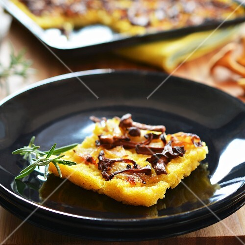 A slice of polenta cake with chanterelle mushrooms and onions on a plate in front of a baking tray