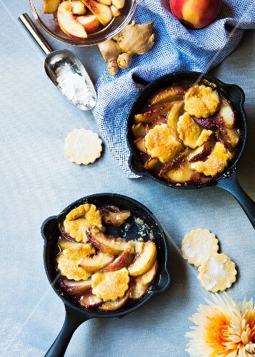 Peach cobbler in small skillets with ginger & cardamon shortbread biscuits