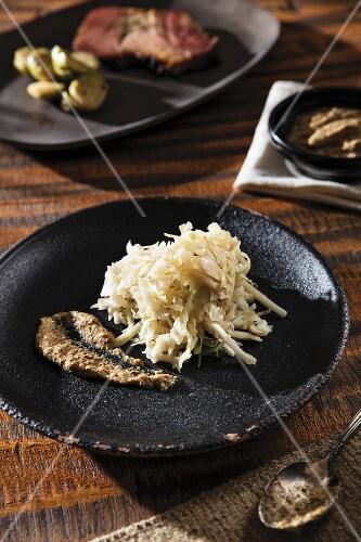 Home-made sauerkraut and mustard on a black plate