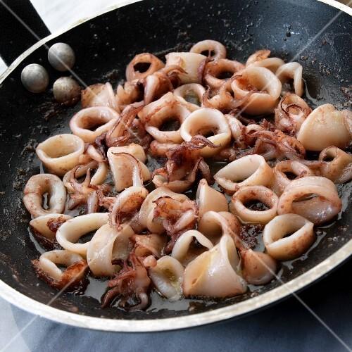 Pan-fried calamari rings in a frying pan