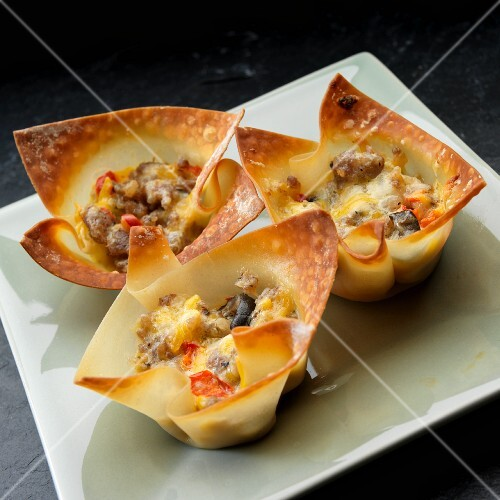 Wanttan bowls filled with sausage, egg, olives and peppers