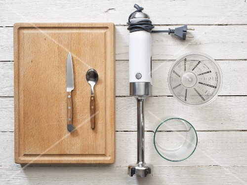 A hand blender, knife, spoon, glass and measuring cup