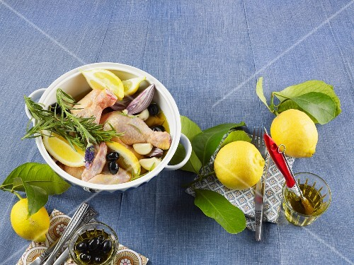 Raw chicken parts with lemon wedges, olives, onions and rosemary