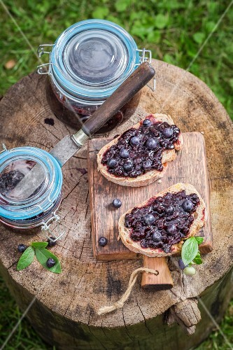 Bread topped with blueberry jam on a wooden board in the garden