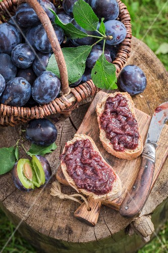 Bread topped with plum jam on a wooden board in the garden