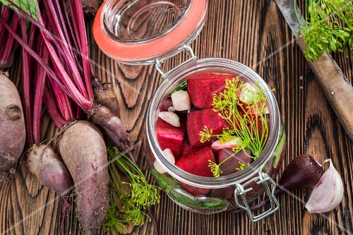 Pickled and fresh beetroot on a wooden crate in the garden