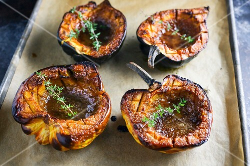 Roasted pumpkins with thyme on a baking sheet