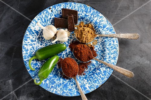 Spices in spoons with chilli peppers, garlic and chunks of chocolate on an enamel plate