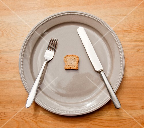 A symbolic image for dieting: a plate with cutlery and a tiny slice of toast