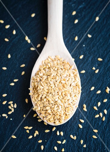 Golden flax seeds on a wooden spoon (seen from above)