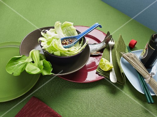 An arrangement of salad, fish, noodles and soy sauce from Asia