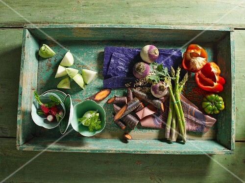 A vegetable crate with asparagus, turnips, peppers and tomatoes