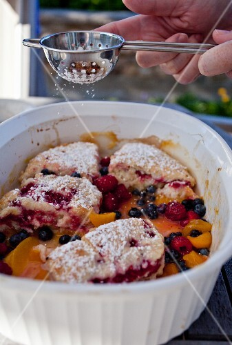 Peach, raspberry and blueberry cobbler being dusted with icing sugar
